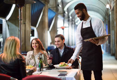 Afro waiter taking table order and smiling Royalty Free Stock Images