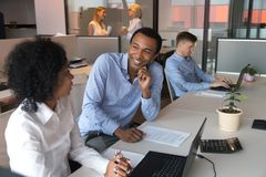 Afro woman and black man colleagues communicating during working day stock photos