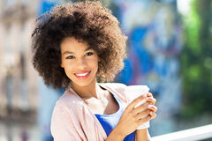 Afro woman with coffee to go. Outdoors