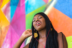 Afro woman listing to music on colorful background Stock Image