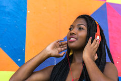 Afro woman listing to music on colorful background Stock Photo