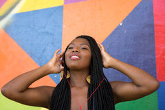 Afro woman listing to music on colorful background Stock Photos
