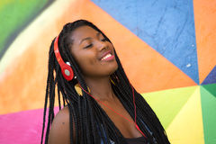 Afro woman listing to music on colorful background Royalty Free Stock Image