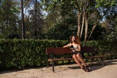 Afro woman reading a book on a bench. Young afro woman reading a book on a bench at a park on a sunny day Royalty Free Stock Photos