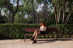 Afro woman reading a book on a bench. Young afro woman reading a book on a bench at a park on a sunny day Royalty Free Stock Photography