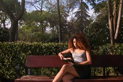 Afro woman reading a book on a bench. Young afro woman reading a book on a bench at a park on a sunny day Stock Photography