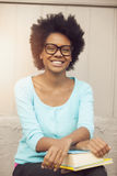 Afro woman smiling with books Stock Photo