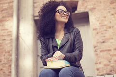Afro woman smiling with books. Afro woman smiling wearing glasses with books Royalty Free Stock Images