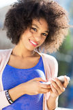 Afro woman using mobile phone Stock Photo