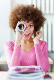 Afro woman using newspaper as spyglass. Beautiful African American woman at cafe Royalty Free Stock Photography