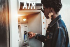 Afro woman is using an outdoor ATM stock image