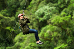Afro Woman On Zip Line Against Blurred Forest. Adult Slim Afro Woman On Zip Line In Ecuadorian Rainforest Nearby Banos De Agua Santa stock image