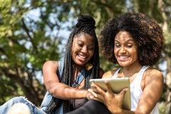 Afro women using tablet computer in the park Royalty Free Stock Photos