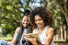 Afro women using tablet computer in the park Stock Image