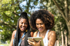 Afro women using tablet computer in the park Royalty Free Stock Image