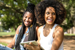 Afro women using tablet computer in the park Royalty Free Stock Photography