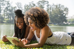 Afro women using tablet computer in the park Royalty Free Stock Images