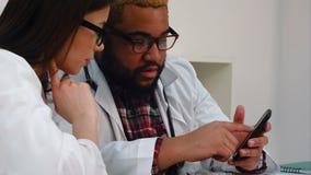 Afroamerican врач показывая что-то на телефоне к довольно женскому коллеге акции видеоматериалы