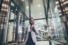 Afroamerican biznesmen opowiada na telefonie w nowożytnej szklanej windzie Zdjęcia Stock