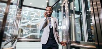 Afroamerican biznesmen opowiada na telefonie w nowożytnej szklanej windzie Zdjęcie Stock