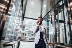 Afroamerican biznesmen opowiada na telefonie w nowożytnej szklanej windzie Zdjęcie Royalty Free