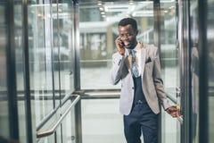 Afroamerican biznesmen opowiada na telefonie w nowożytnej szklanej windzie Zdjęcia Royalty Free