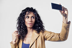 Afroamerican black woman making selfie photo. Black long hair, leather jacket Royalty Free Stock Images