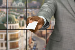 Afroamerican businessman gives visit card. Royalty Free Stock Image