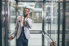 Afroamerican businessman in modern glass elevator talking on phone. Businessman in modern glass elevator talking by the phone Stock Photo