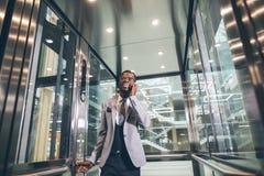 Afroamerican businessman in modern glass elevator talking on phone. Businessman in modern glass elevator talking by the phone Royalty Free Stock Images