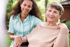 Afroamerican carer and ill patient. Image of afroamerican carer and ill female old patient stock images