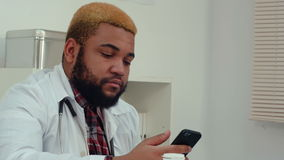 Afroamerican doctor using mobile phone at the work desk. Close up shot. Professional shot on BMCC RAW with high dynamic range. You can use it e.g. in your stock video footage