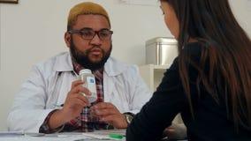 Afroamerican doktor som ordinerar preventivpillerar till den kvinnliga patienten och förklarar dosering lager videofilmer