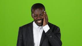 Afroamerican facet w kostiumu doświadcza surową migrenę zielony ekran zdjęcie wideo