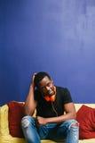 Afroamerican facet z hełmofonami, domowy czas wolny Obrazy Stock