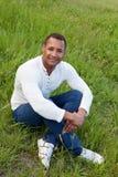 Afroamerican faceta obsiadanie na trawie Fotografia Royalty Free