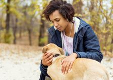 Afroamerican girl in autumn park playing with her dog.  stock images