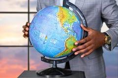 Afroamerican hållande jordklot nära fönster Arkivbilder