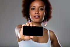 Afroamerican kobieta pokazuje telefon komórkowego Fotografia Stock