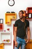 Afroamerican mężczyzna w hełmofonach w domu, czas wolny Zdjęcia Royalty Free