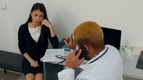 Afroamerican male doctor talking on the phone making his female patient wait stock footage