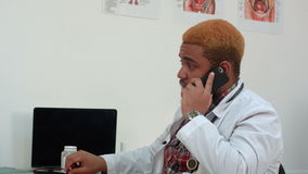 Afroamerican male doctor talking on the phone making his patient wait stock video