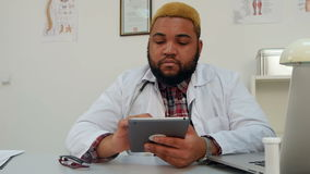 Afroamerican male doctor using digital tablet stock footage