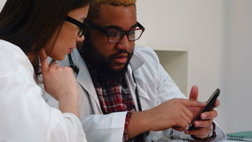 Afroamerican physician showing something on the phone to pretty female colleague. Close up shot. Professional shot on BMCC RAW with high dynamic range. You can stock video footage