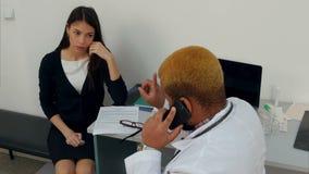 Afroamerican samiec doktorski opowiadać na telefonie robi jego żeńskiemu cierpliwemu czekaniu zbiory