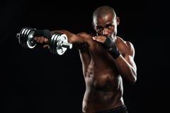 Afroamerican sporty obsługują pozować jak walka z dumbbells Zdjęcia Stock