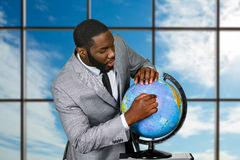 Afroamerican studies globe at daytime. Employee with globe beside window. The global plan. Somewhere amidst the ocean Royalty Free Stock Photos