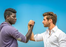 Afroamerican and white man. Afroamerican and caucasian men shaking hands - peace,teamwork,collaboration,diversity concept stock image