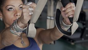 Afroamerican woman is having a training on straps in the gym. Young lady in blue sportswear and silver accrssories is doing TRX low row exercises. Sportswoman stock footage