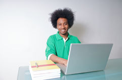 Afroamericano con il computer portatile ed i manuali Fotografie Stock Libere da Diritti